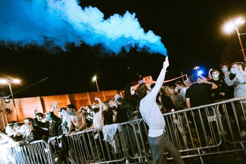 Fêtard tenant un fumigène à la soirée Border City. Crédit : Clement Beny